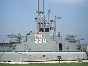 "The conning tower fairwater of U.S.S. Cod, in a photograph taken 6 September 2001 at her berth in Cleveland, Ohio. This is an excellent example of the ""covered wagon"" bridge cutdown performed on many Gato class submarines to reduce the surface silhouette. The painted flags, representing wartime kills—and, in the case of the cocktail glass, a rescue—and the hull number would not have been present during wartime. Note the single-mount 40-mm guns on the forebridge and cigarette deck. Note also the SJ radar antenna behind the extended periscopes, and the retracted SD air warning radar on the aftermost mast, just forward of the after Target Bearing Transmitter. In a combat situation, this mast would be extended. Cod represents one of the finest restoration efforts to be found."